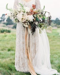 This cascading bouquet of peonies, ranunculus, clematis recta, foxglove, acacia, cafe latte roses, and black elderberry foliage is what every boho bride's dreams are made of.