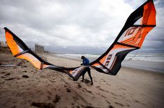 John Pettine, of San Diego, hauls in his kitesurfing kite under heavy winds along Pacific Beach on April 13 in San Diego. Wind and rain pounded areas of Southern California Friday, part of a cold storm that was expected to leave up to 14 inches of snow in southern mountains. (Gregory Bull/Associated Press)