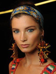 Dolce & Gabbana beweist Mut zur Farbe! Inspiriert von den 60er-Jahren, ließ das Designerduo seine Models mit kunterbunten Tüchern im Haar auf dem Catwalk laufen. Die lässige Frisur lässt sich ganz einfach nachstylen - Schritt 1: einen Dutt machen. Schritt 2: ein schönes Tuch umwickeln. Und schon ist die coole Frisur fertig!