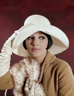 Damesmode, hoeden. Model met witte hoed, witte handschoenen en een bonstola (kunstbont). Nederland, zonder jaartal [ca. 1968].