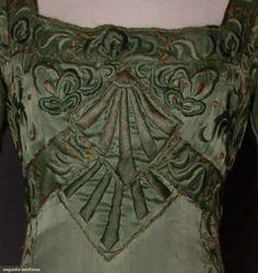 ARTS & CRAFTS EMBROIDERED GOWN, c. 1910 Sage green silk satin, sage embroidery, ball fringe hem trim; t/w 1 camel wool day dress, black velvet & lace trim. Detail