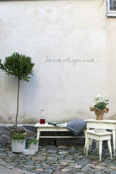 Muurtekst 'Love is all you need' van staaldraad
