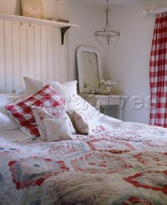 A country bedroom in red and white  wood panelling  double bed  patchwork quilt cover  cushions and