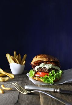 Burger and Chips - Delicious burger with fried chips on a wooden table.