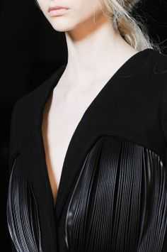 Black wool dress with cut out shapes and pleated leather inserts; striking fashion details // Marco De Vincenzo AW13