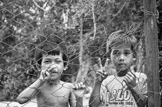 "Two Cambodian boys at a raggedy fence flash peace signs at the camera.  It's interesting how children born so many decades after the birth of the ""peace sign"" and the era in which it was so heavily used, still always seem to know its meaning.  Adults forget that our children are observing the world, and all children want World Peace.   ~Skye"