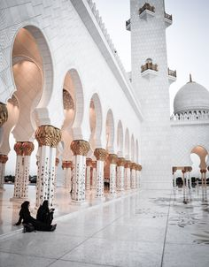 Two women in traditional clothing at the Zayed Grand Mosque in Abu Dhabi.