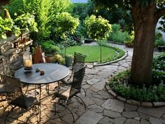 Flag stone patio. Love the treatment around the tree! Would be good where we get oak tree shooters coming up in the grass...