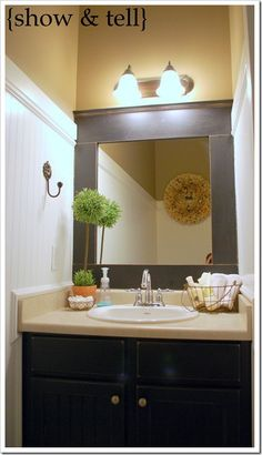 TOTALLY LOVE the mirror frame!  Someday when I get my house.... the spare Bathroom is going to have a mirror, beadbord cupboards, and beadboard walls just like this one!.  And look in the mirror to see what she hung above the toilet.  Also a SUPER cute way to add a little style!