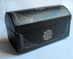 B10797 £25 inc UK post. Offers welcome. A vintage trunk shaped gilt tooled leather covered casket with damask type black lining, standing on four metal supports. The casket is structurally sound but there is some wear to the leather covering (see photographs) particularly to the back. The gilt tooling has worn a little in places. The casket measures approximately 8.75in by just over 4.75in at the base. For further info/photos, please contact us