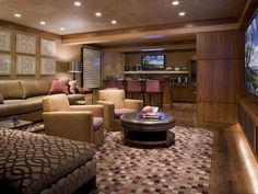 """Sophisticated Man Cave: From family movie night to prime-time sporting events, the geometric patterns and artwork, a commanding 85"""" plasma TV and a full bar area set the stage for everyday this media room.  From HGTVRemodels.com"""