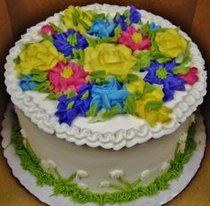 Spring buttercream flowers on layer cake in yellow, pink, blues, green.