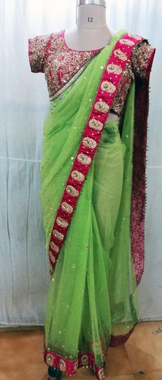 Gorgeous Green Shimmer Net Mirrorwork with Fuchsia Embroidered border and Heavily Embellished Fuchsia Blouse of Paisely Motifs and Matching Colored Stones..All by AVEN