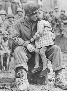 US Signal Corp Photo Tec-4 Elvin Harley of Kalamazoo, Michigan, of the 3rd Armored Division, gets a peck on the cheek from a little French girl while listening to the 9th Armored Division Band near Aboncourt, France.