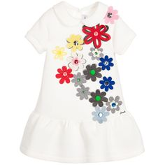 Girls fabulous white dress by Simonetta, featuring colourful, floral appliqués scattered across, with large, sparkling gemstones at their centres. Made in soft neoprene, the dress has a dropped waist with a flared skirt below and the designer's silver metal logo sewn on one side. There is a concealed zip fastener at the back.