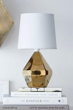 Bordlampe med gullfarget fot av keramikk og tekstilskjerm. Høyde 33 cm. Ø 18 cm. Liten sokkel. <br><br>