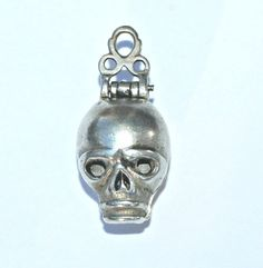 Skull Pomander Pendant | A rare silver death's head skull pomander pendant, circa 1680 - 1700, designed to remind its owner to prepare for death by leading a virtuous life. The hinged skull, with pierced eyes, opens to reveal compartments for perfumes or spices - those commonly used to mask unpleasant odours included musk, lavender, mace and nutmeg.