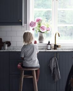 my scandinavian home: Grey kitchen cabinets, white tiles and peonies in a beautiful Swedish family home / photo - Emily Slott