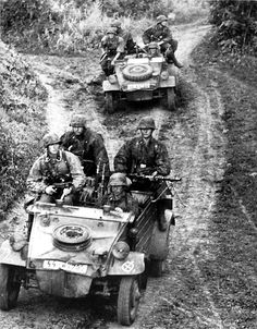 SS troops riding in their VW Type 82 Kubelwagens. Note the damage to the vehicles bodies, indicating the rough service these vehicles endured.