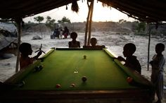 Pakistani boys, whose families were displaced by 2010 floods from a village in Pakistan's Sindh province, play pool in a slum on the outskirts of Islamabad, Pakistan, July 10, 2012. (Muhammed Muheisen/Associated Press)