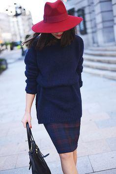 Acheter la tenue sur Lookastic:  https://lookastic.fr/mode-femme/tenues/pull-surdimensionne-bleu-marine-jupe-crayon-sac-fourre-tout-noir-chapeau-rouge/1218  — Chapeau en laine rouge  — Pull surdimensionné bleu marine  — Jupe crayon écossaise bleue marine  — Sac fourre-tout en cuir noir