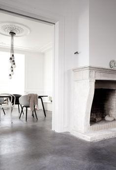 estrich-der fußboden aus estrich grau im industrial style für moderne wohn esszimmer mit esstisch schwarz und kamin aus weißen ziegeln