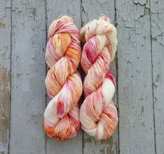Hand dyed sock yarn. This yarn is randomly dyed with a light orange and pink…