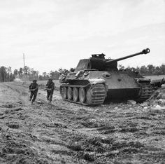 BRITISH ARMY NORMANDY 1944 (B 6049) Men of the Durham Light Infantry, 49th (West Riding) Division 'advance' past a knocked-out German Panther tank during Operation 'Epsom', 27 June 1944.
