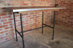 Stół Pipe to oryginalne połączenie drewnianego blatu opartego na nogach wykonanych z rur stali czarnej.
