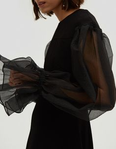 NOTE: UK SIZES LISTED. See sizing guide for conversion information.  Contemporary dress from Rejina Pyo in Black. Round neckline. Concealed back zip closure. Slightly dropped shoulders. Voluminous long sleeves in a sheer organza. Contoured seams . Flare