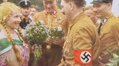 A member of the League of German Maidens -- the female faction of the Hitler Youth movement -- offers flowers to Hitler. (Credit: SWNS.com)