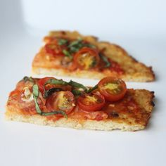 Cauliflower Pizza Crust -   -Nonstick spray -2 1/2 cups grated cauliflower (about 1/2 a large head) -1 large egg -1 1/4 cups shredded part-skim mozzarella cheese -2 tbsp grated parmesan cheese -Salt and ground black pepper -1/4 cup tomato sauce -1 cup grape tomatoes, sliced in half -2 cloves garlic -1/4 tsp crushed red pepper flakes -Fresh basil leaves, optional