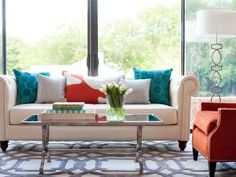 Create a lively living room with energetic shades. Designer Abbe Fenimore mixes decorative accents in color-wheel opposites peacock blue and tangerine to enliven this living room's color palette. For a softer look, try tangerine and mint. Image courtesy Abbe Fenimore of Studio Ten 25