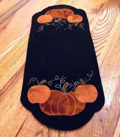 Pumpkin Trio Table Mat by Lisa Bongean. The pattern is full size and it has full instructions for making it and a list of what you need on the back of the pattern. Finished size is 8.5 by 18.5.  The wool is not included with the pattern. We have wool fabric by the piece here:
