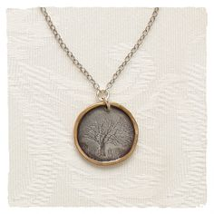 A mighty oak tree is engraved in all its splendid detail on our mixed metals pendant. Exquisitely rendered, this nature scene sits on a disc of oxidized sterling silver with a 14kt gold fill edge. Sterling silver cable chain.