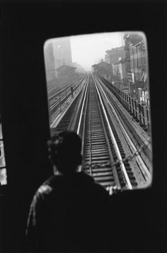 Elliott Erwitt:  I like this photo because I think it looks really cool with how the window frames the outside city and the tracks and I like how the kid is looking out
