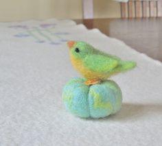vilten groene en gele vogel / vrouwelijke painted bunting zittend op een pompoen…