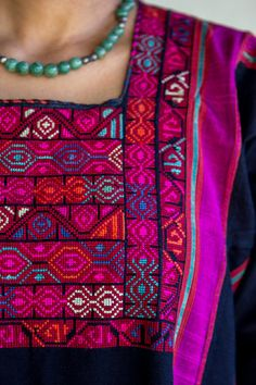 A traditional black Palestinian dress of a young woman, with bright colored intricate embroidery. Cotton with Magenta silk stripes From about 1960.  A very unique and beautiful dress in an excellent condition! Can be used and warn.   SIZE:  US size – S– L 8-12 Europe size – 36-42  Bust – 46 = 118 cm Hips – 50 = 128 cm  Length of the dress from shoulder to floor – 53 = 135 cm  Sleeves width, circumference at widest part – 16 = 42 cm Sleeves width, circumference at nerrowest part – 9.5 = 25 cm…