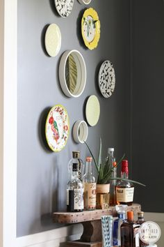 Gallery wall of plates and mirrors, love the liquor bottles displayed on the wooden pedestal