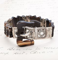"1860s Scottish Silver and Agate Belt Bracelet. Each hinged link is made of carved agate ranging in color from white to brown to black. The bracelet fastens just a like a belt, so the length can be adjusted between 7"" and 8""."