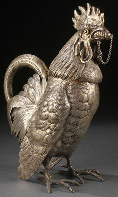 A SILVERED FIGURAL ART DECO ROOSTER COCKTAIL SHAKER, GERMAN, CIRCA 1920'S. Modeled as the full figure of a standing cockerel. The removable head set with glass eyes, internal strainer and pouring spout with attached stopper with integral beverage reserve. Overall realistically sculpted with fine detail and overlapping chased feathers, with scroll tail feather form handle and raised on talon feet.