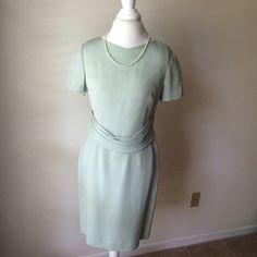 Talbots silk dress This is a gently used silk dress by talbots. It is a lovely pale green color (think sea foam green). It has short sleeves, a modest v-neck, a piece of draped fabric in the front, a hidden back zipper, and a back slit. Dry clean only Talbots Dresses