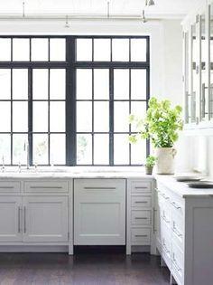 lightest grey cabinets, brass pulls, white counters, dark hardwood floor, glass uppers, black window trim.