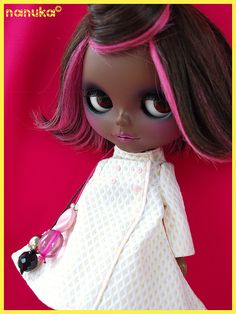 Black Blythe doll with pink-streaked hair.