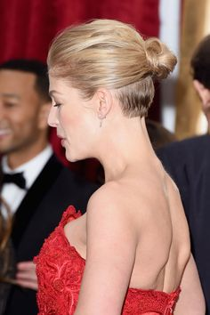 16 Oscars' Red Carpet Beauty Looks That Made Our Hearts Sing #refinery29 -Rosamund Pike- Raking her locks back and up into a textured, slightly rumpled high bun, her growing-out shave was on full display.