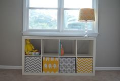 Two ideas here: cube unit below the window (in the living room, this would provide a great storage area for toys), and the bins covered in fabric! Love it!