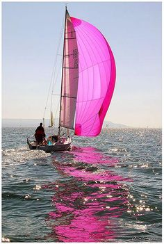 Beautiful reflections of a pretty pink sailboat! What a terrific photograph of the sailboat and its'pretty pink sail!