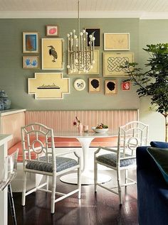 """Depending on the size of your space, a breakfast nook can be either an """"extra"""" dining area or, in smaller apartments, the main dining event. Regardless, a gallery wall centered on the space makes the area feel like its own mini room. A mix of prints and paintings makes for a fun conversation piece when dinner guests linger around the kitchen."""