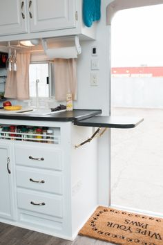 The kitchen counter on this revamped trailer is hinged and kept up as needed, but folds down to store flat against the cabinets.