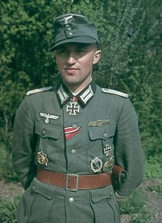 A young, highly-decorated German Army Oberleutnant posing with an ambiguous, faint smile. He is wearing the First and Second Class Iron Cross, the Order Of The Knight's Cross Of The Iron Cross, as well as the Order of the German Cross (all awarded for continuous bravery before the enemy). He was also awarded the Infantry Assault Badge and the Close Combat Clasp, as well as two decorations that cannot be made out clearly. He is armed with a Czech ČZ Model 27 pistol and holster.